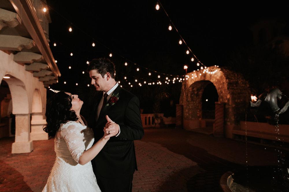 Bride and groom dancing under string lights