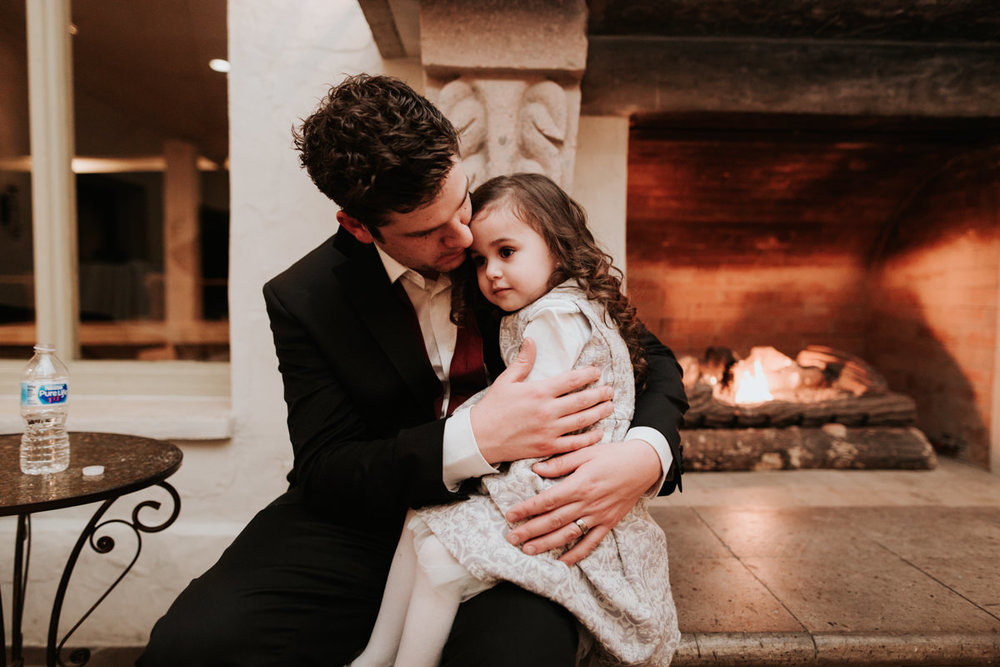 Groom sitting with child on his lap in front of fireplace