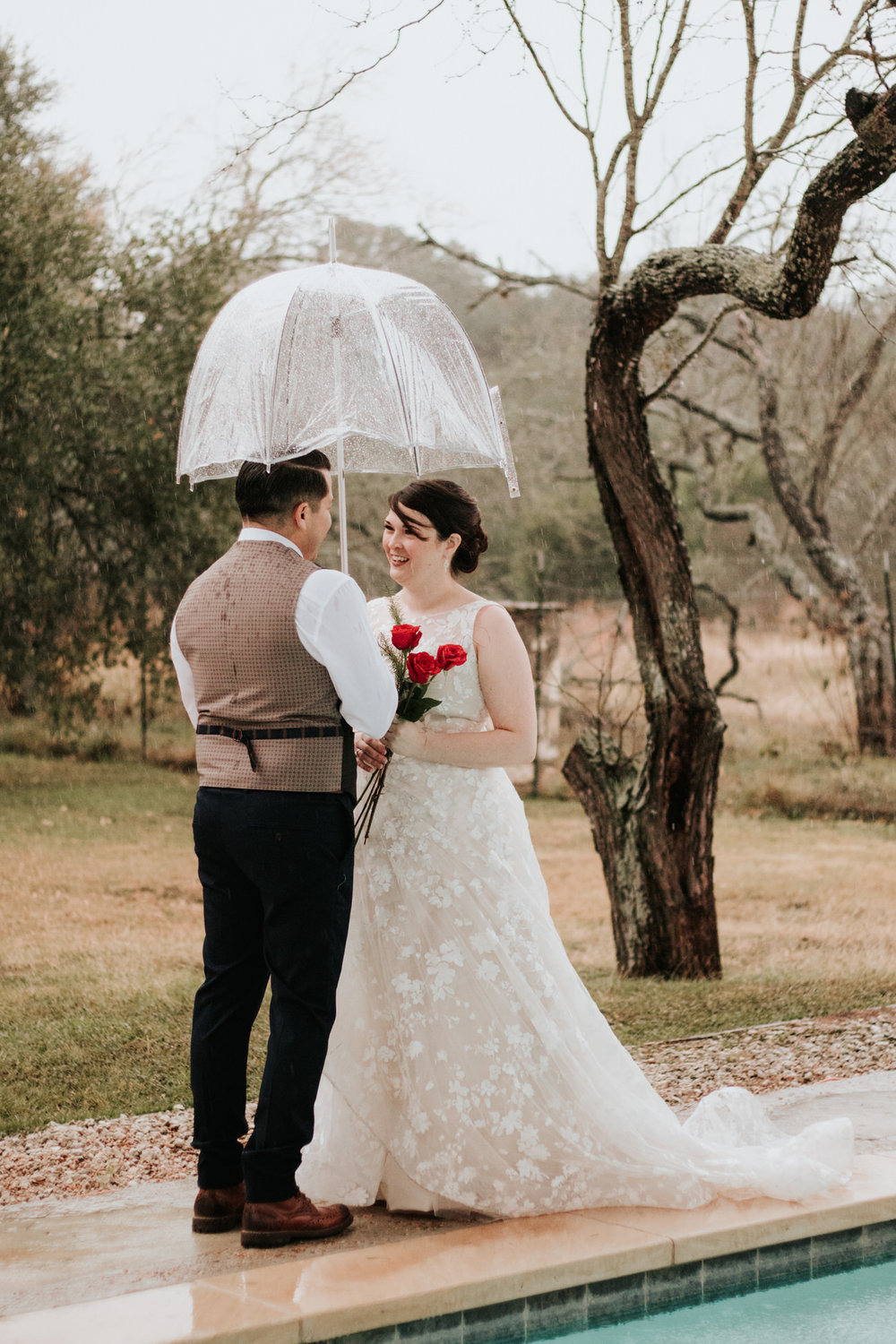 Bride and groom outside in rain under umbrella at Christmas wedding