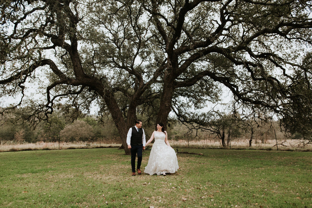 Bride and groom holding hands in front of huge tree