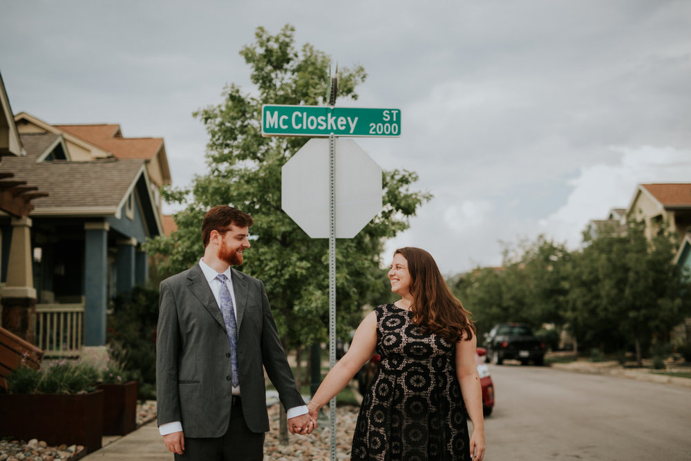 Couple holding hands in front of street sign