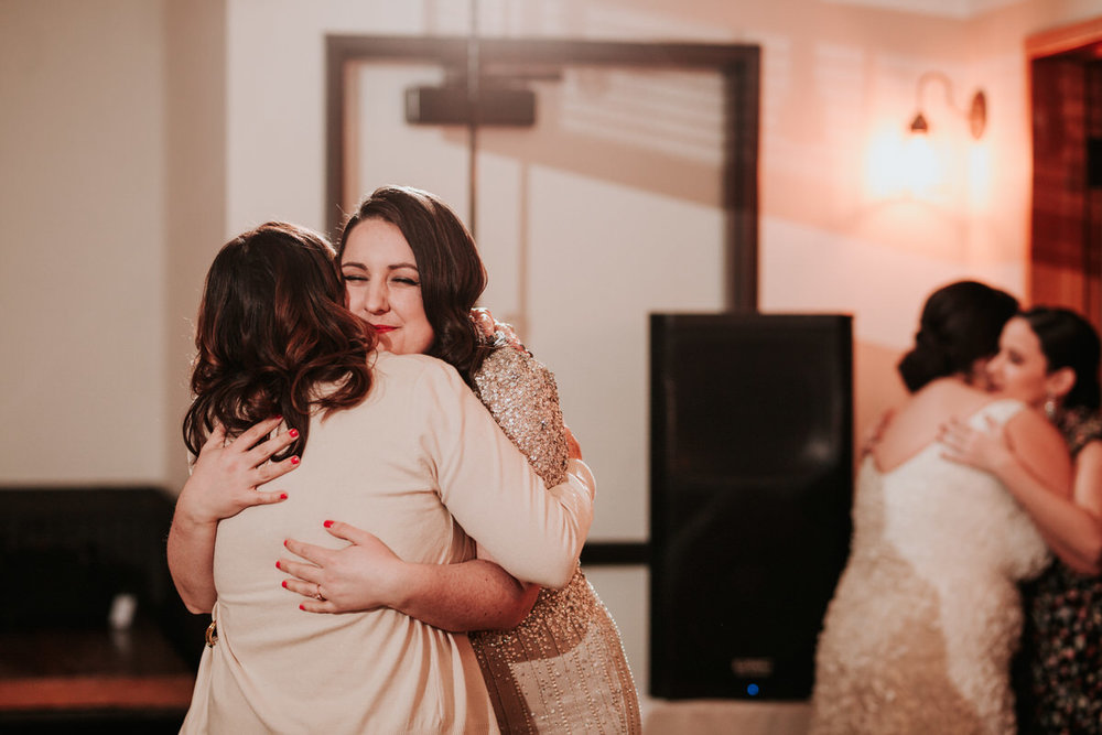 Guests hugging at same sex wedding