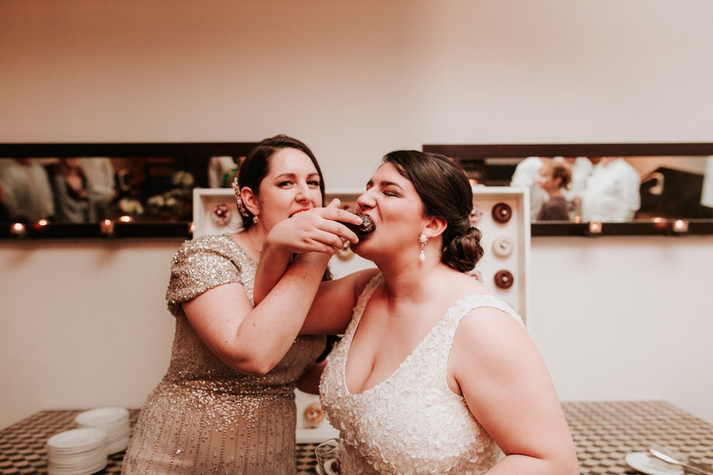 Brides feeding each other mini donuts