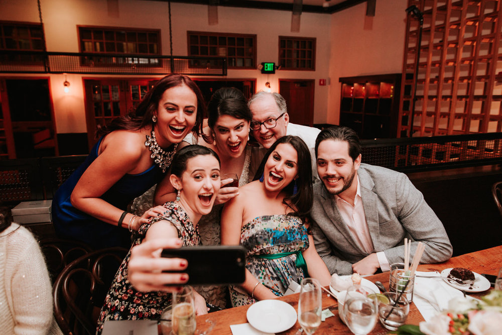 wedding guests at same sex wedding taking a selfie