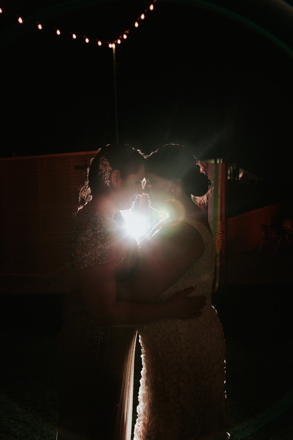 Brides embracing in the dark