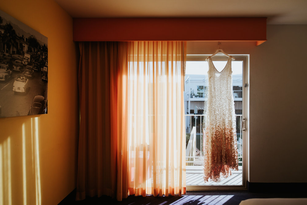 Beautiful wedding dress hanging in sunlight