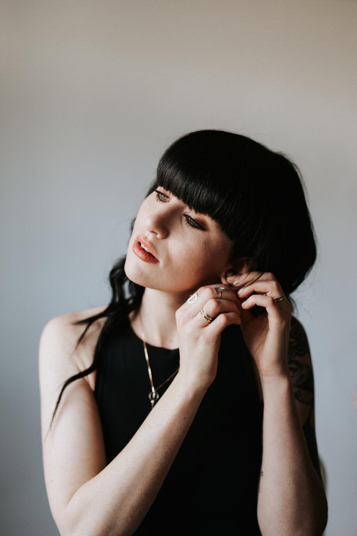 Tattooed model wearing Rebekah Vineyard Jewelry