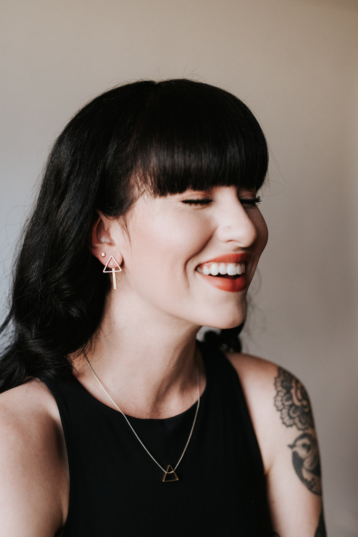 Laughing woman wearing beautiful, geometric Rebekah Vineyard Jewelry