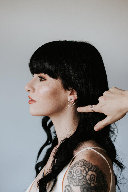 Tattooed woman wearing beautiful, geometric Rebekah Vineyard Jewelry