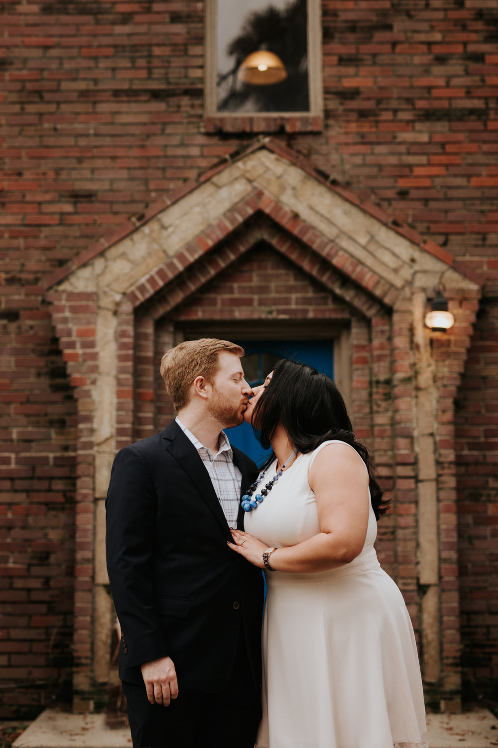 Engaged couple kissing in front of brick building