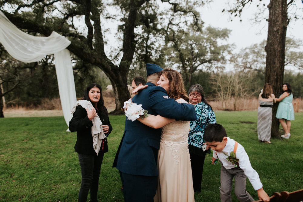 Wedding guests hugging at Pecan Springs Ranch