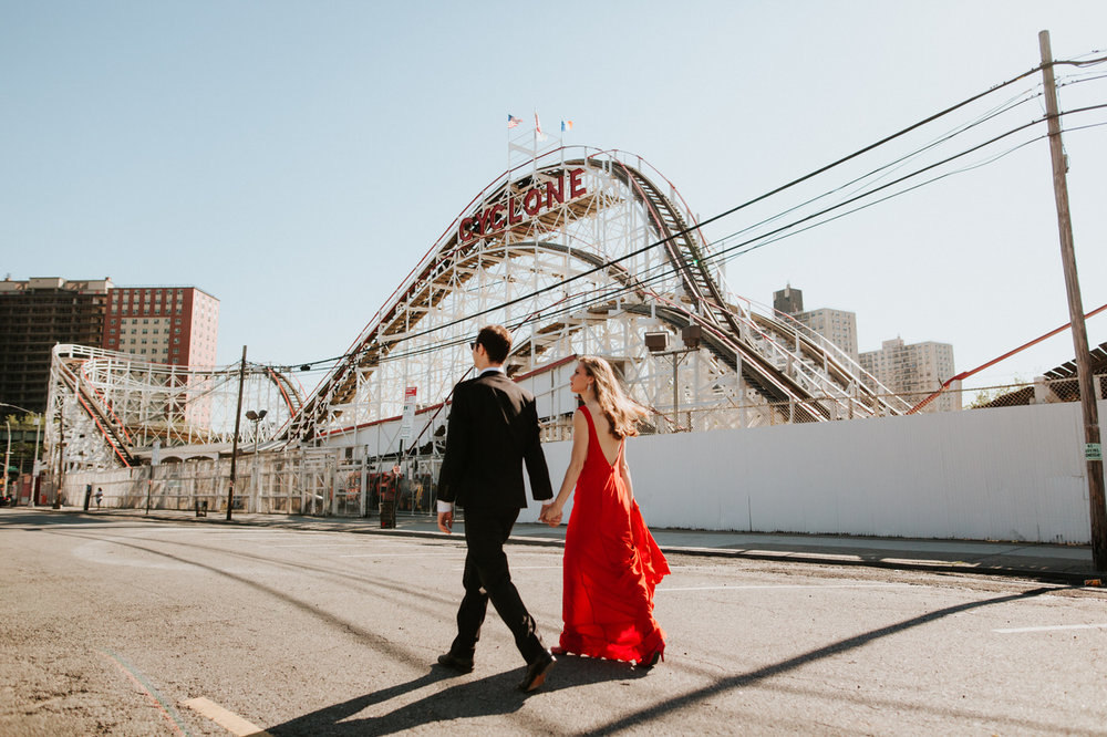 Engaged couple in front of Coney Island roller coaster
