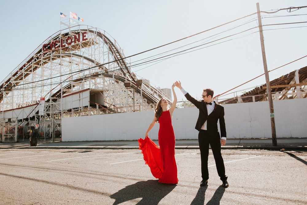Engaged couple dancing in front of Coney Island boardwalk