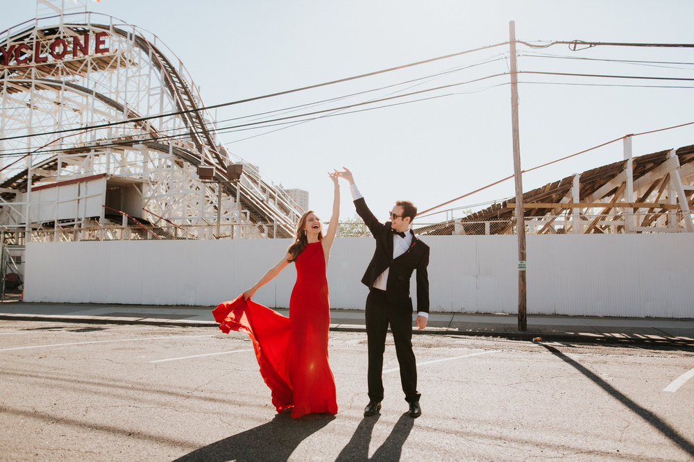 Engaged couple dancing at Coney Island boardwalk