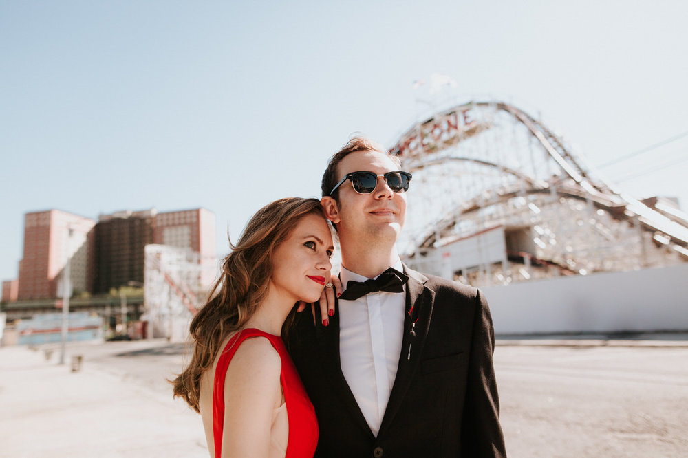 Engaged couple at Coney Island boardwalk in front of roller coaster