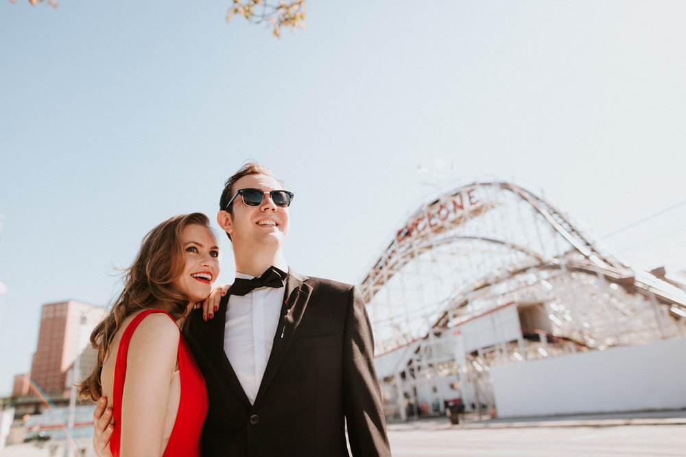 Engaged couple laughing together at Coney Island boardwalk