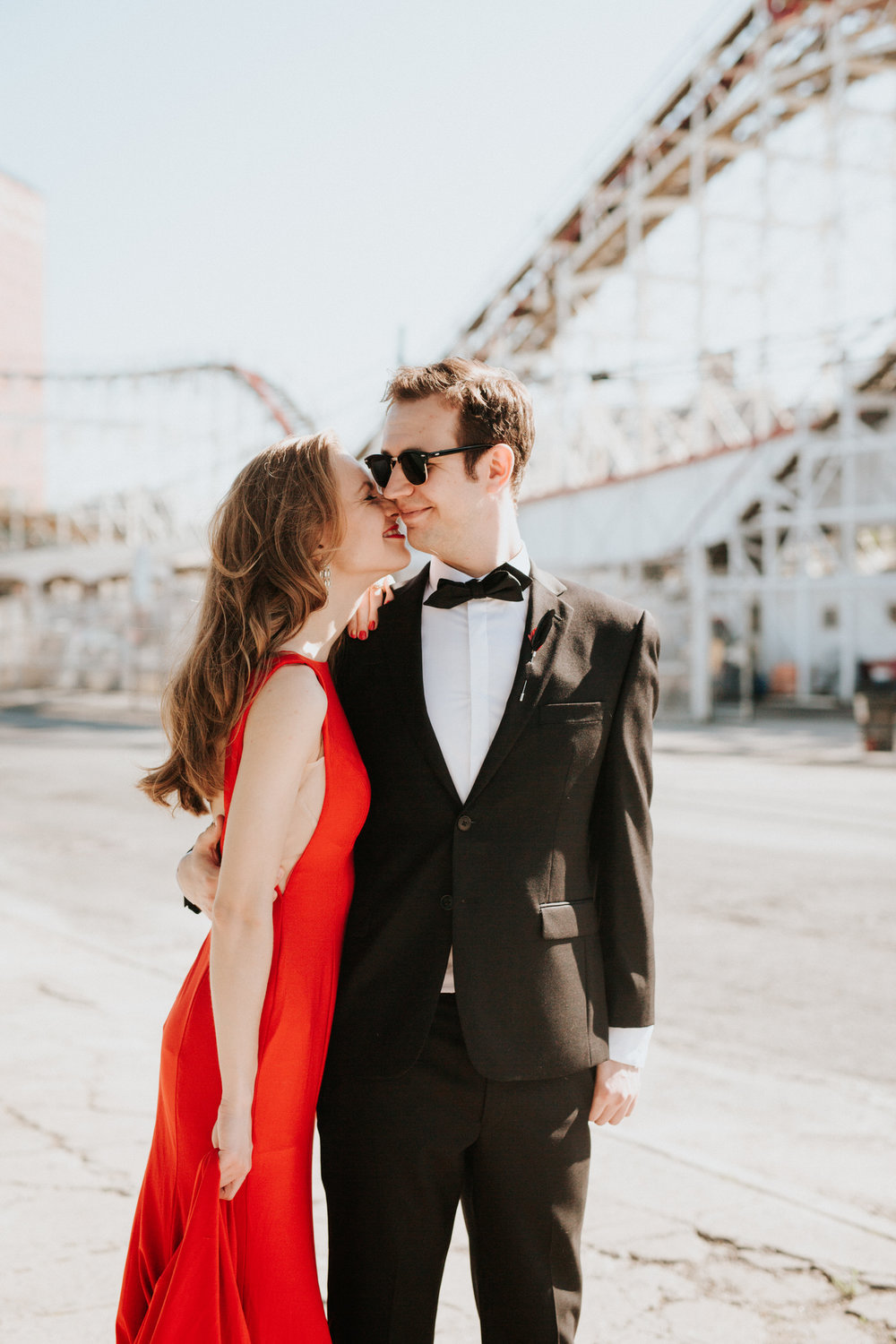 Engaged couple kissing at Coney Island boardwalk
