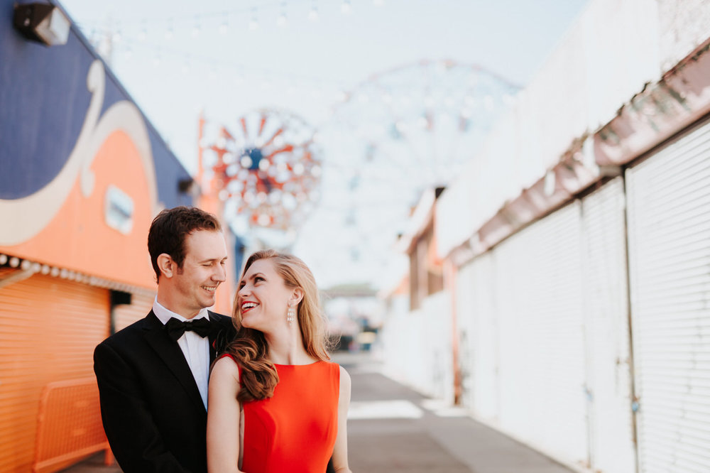 Engaged couple at Coney Island boardwalk in front of ferris wheel