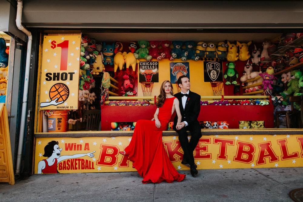 Engaged couple at Coney Island boardwalk with boardwalk games