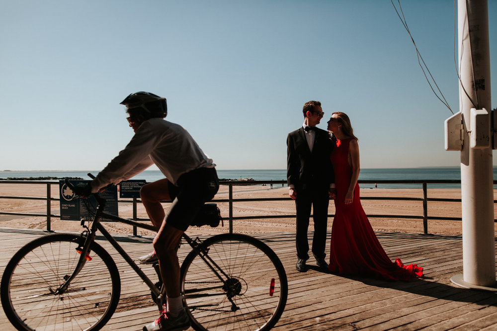 Engaged couple at Coney Island boardwalk with a biker