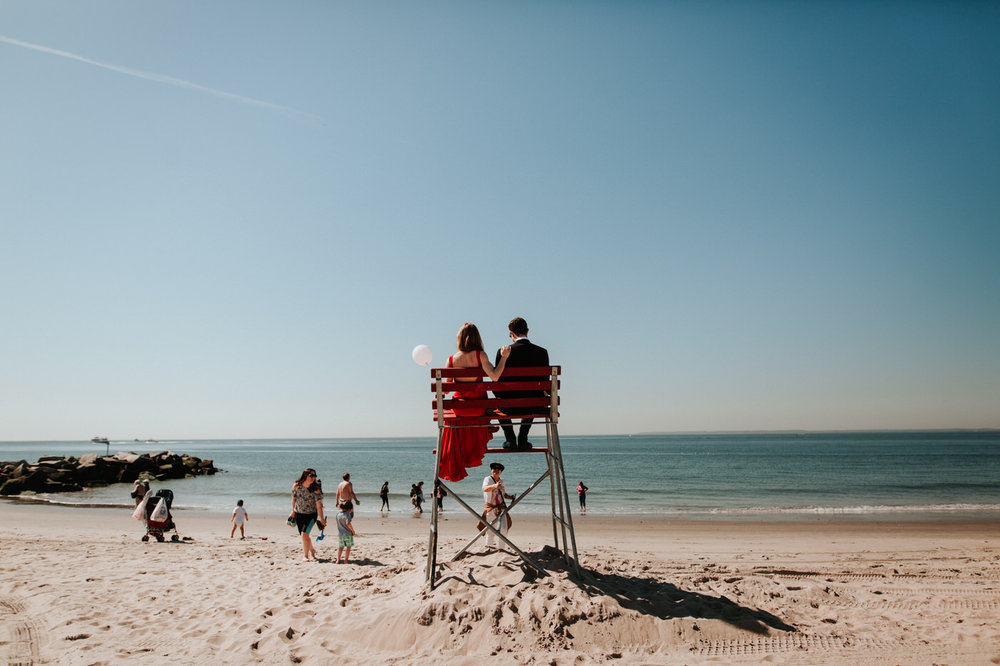 Engaged couple in lifeguard stand at the beach