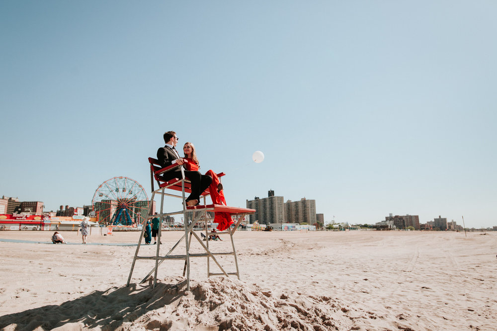 Engaged couple on the Coney Island beach with the full moon