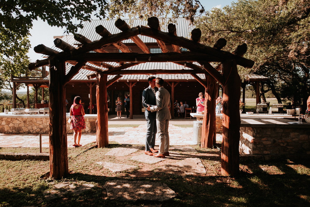 Grooms kissing at Texas hill country wedding