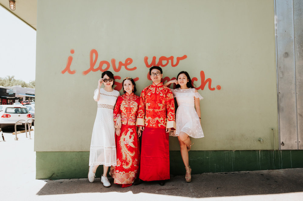 Bride and groom at the downtown Austin i love you so much wall in traditional Chinese wedding outfits