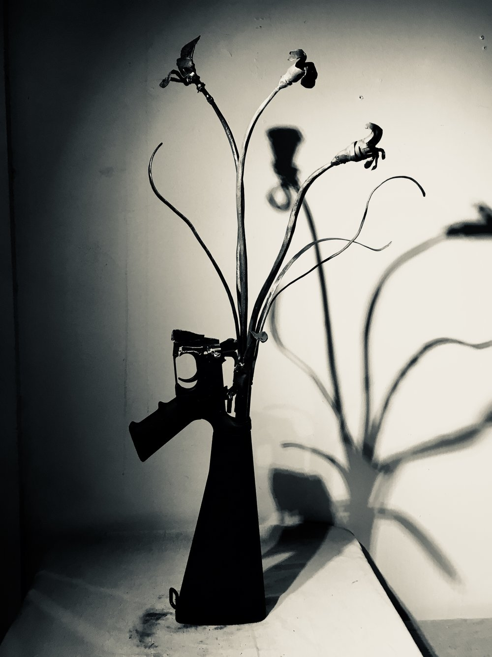 "AR-15 BOUNTIFUL BOUQUET #1     We have created Guns into GARDEN TOOLS for a CHURCH as part of their Ceremony, and later  with DASHBOARD CO OP fro the exhibition at the Marcia Wood Gallery for the Show called UNLOADED  http://www.dashboard.us/unloaded  UNLOADED PROGRAMMING      INTERACTIVE BLACKSMITHING DEMO WITH  CORRINA SEPHORA // PRESENTED BY DASHBOARD     On 5/10/17, Dashboard hosted a contemporary blacksmithing demonstration and performance by Corrina Sephora at Marcia Wood Gallery. During the demonstration, Corrina transformed a gun into a garden tool using contemporary blacksmithing practices, allowing the audience to interact and assist as ""stikers"" in the process.    Artist Statement: ""This act illustrates the old saying 'swords into plough shares' by transforming 'guns into garden tools'. This transformation is an act of creativity from a tool of death and destruction. The creation and transformation of one tool (the gun) into another tool (the garden tool) through fire and forging. Using the four elements the blacksmith in ancient history was once considered a diviner, healer, judge and even a sorcerer, as well as one who made functional objects, sculptures, divination tools, and farming tools. This contemporary interactive performance and teaching session is statement of peace, creativity and community. The interactive work allows people to put their life force, energy or NYAMA into this transformational forging experience.""   --Corrina Sephora"