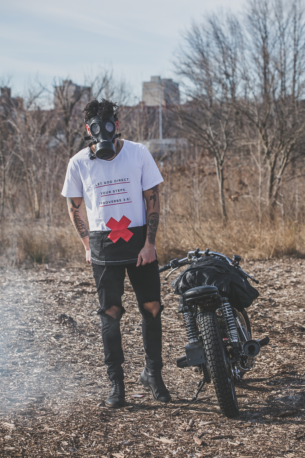 tattooed model in Anchored Apparel with motorcycle and gas mask