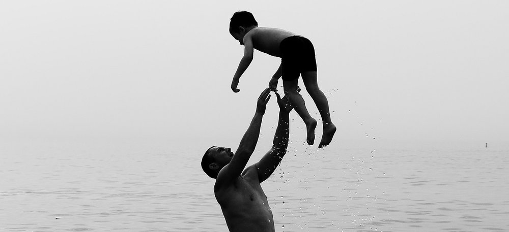 man-throwing-son-in-water.jpg