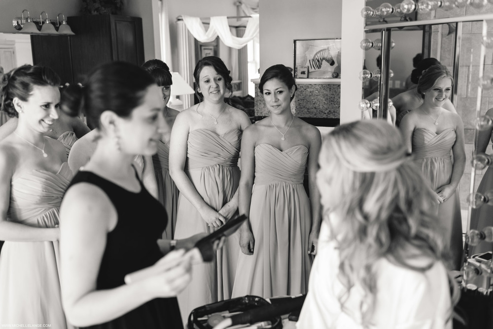 Bridesmaids Looking on While Bride Gets Ready.jpg