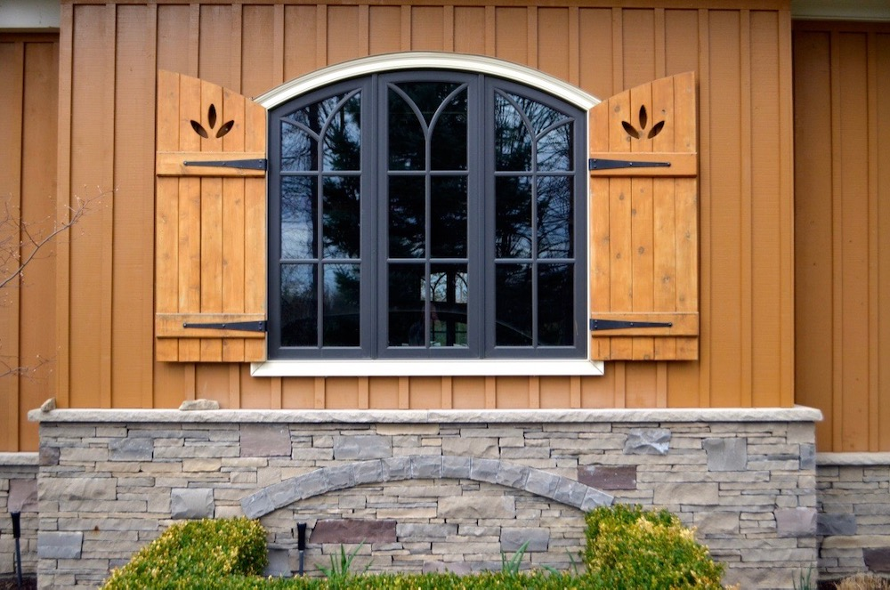 custom home board and batten shutters cedar arched top window stone skirt.jpeg