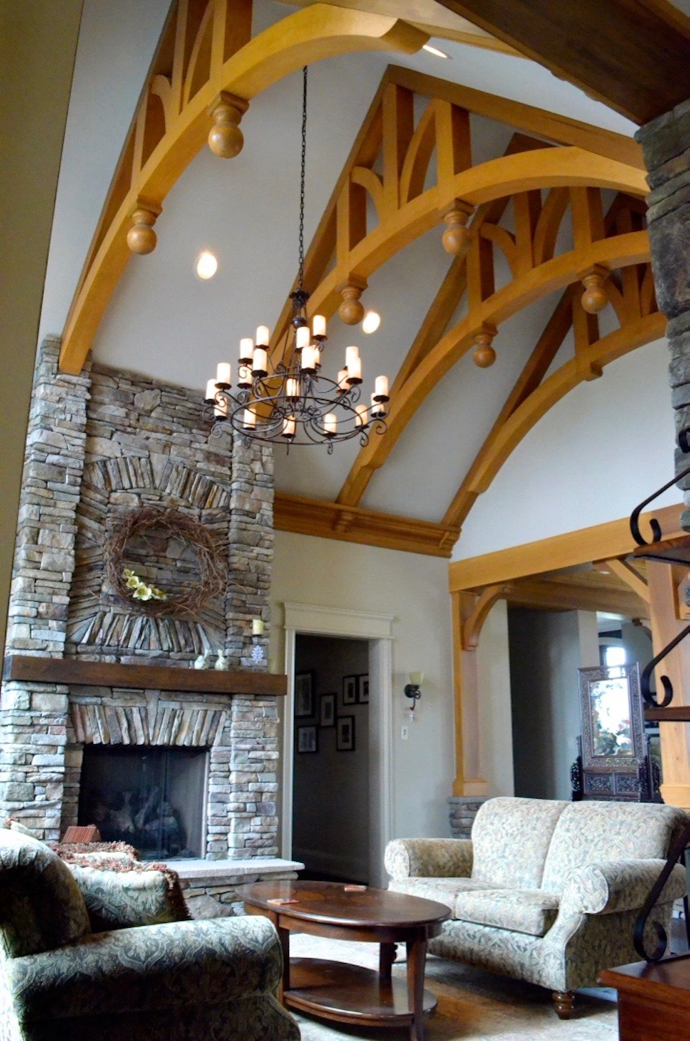 custom home decorative arched beams stone fireplace great room living room.jpeg