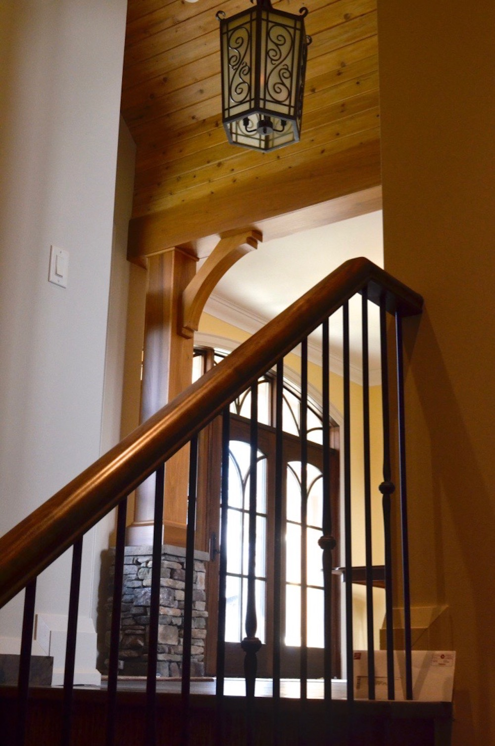 custom home stair metal pickets wood cap arched top door tongue and groove.jpeg