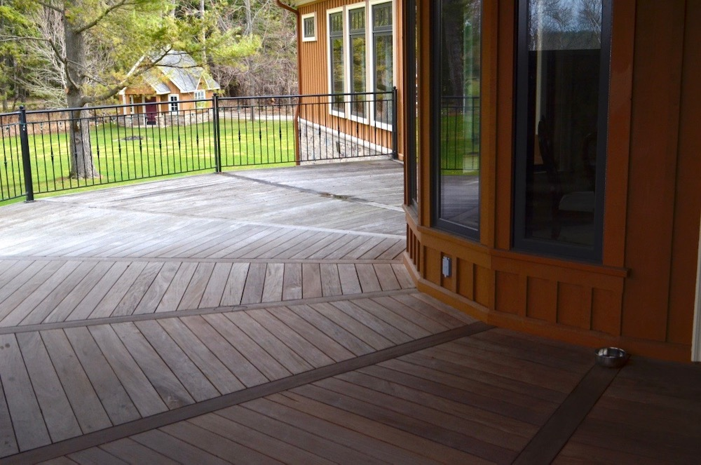 ipe deck segmented brown board and battten black metal railing.jpeg