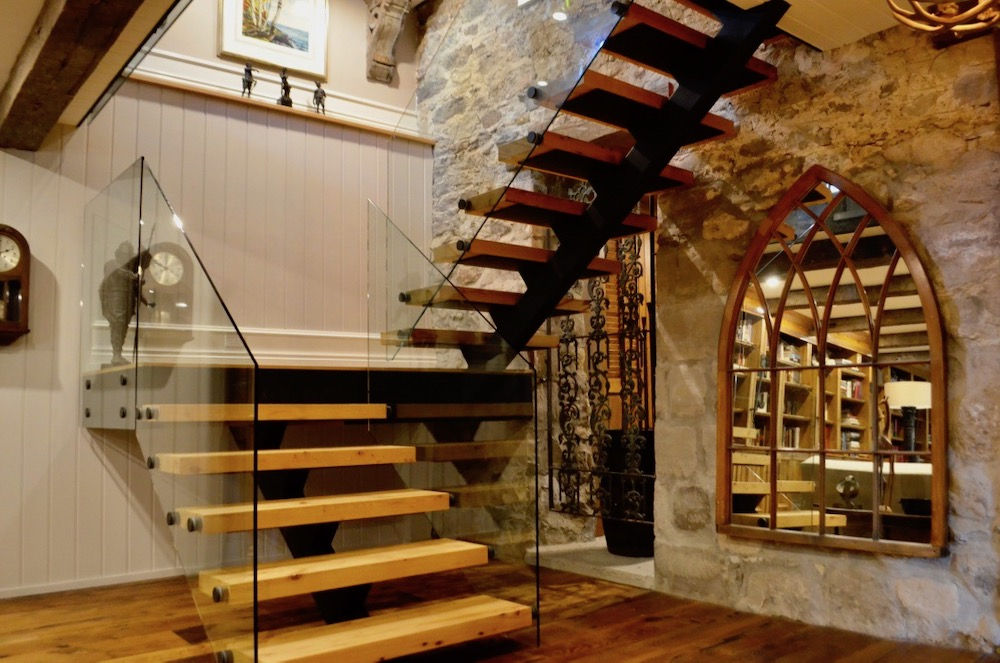 stone farmhouse renovation steel stair timber tread open riser glass railng.jpeg