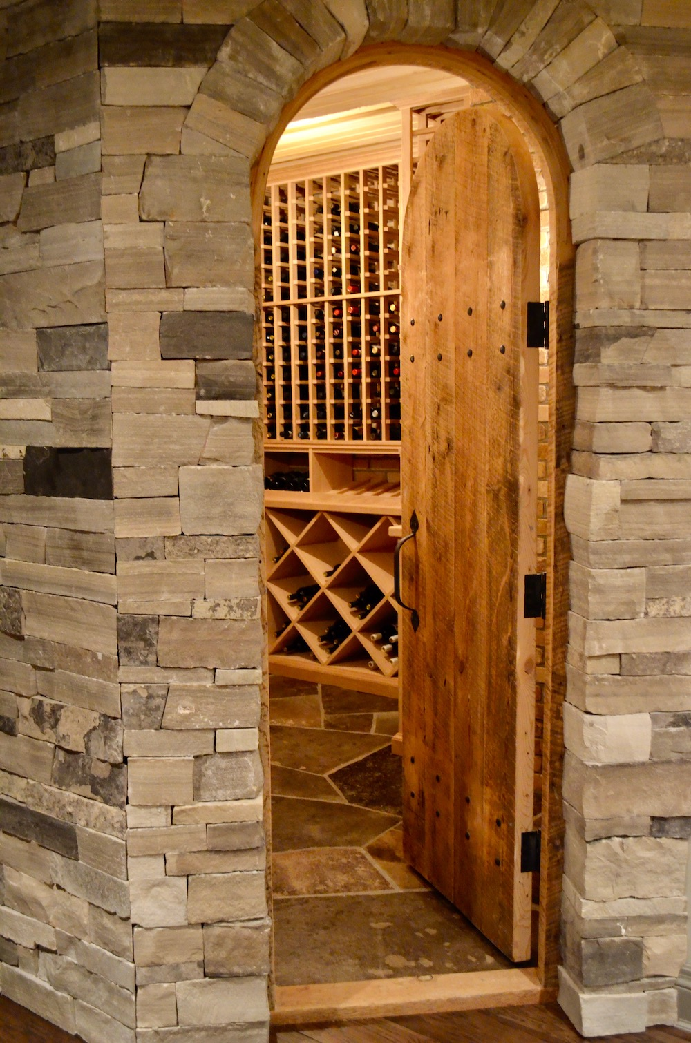 wine cellar stone arched top door rustic stone flooring.jpeg