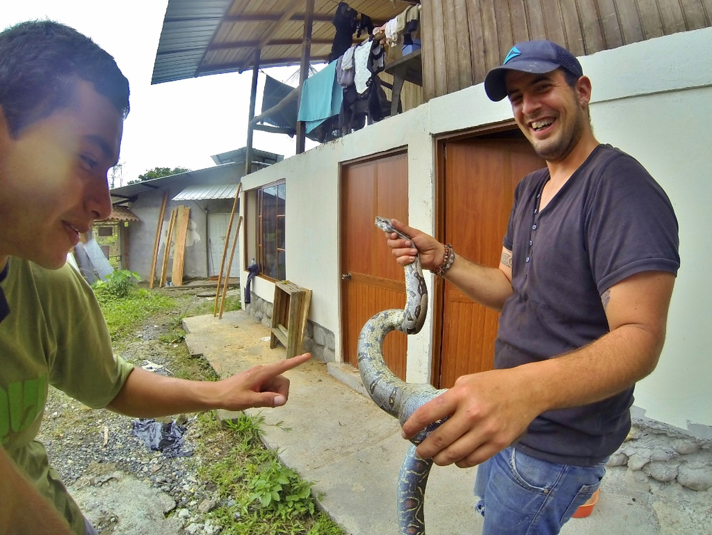 Agustín (right), a volunteer from Spain, tries to help Cristian (left), a staff zookeeper, get over his fear of snakes.