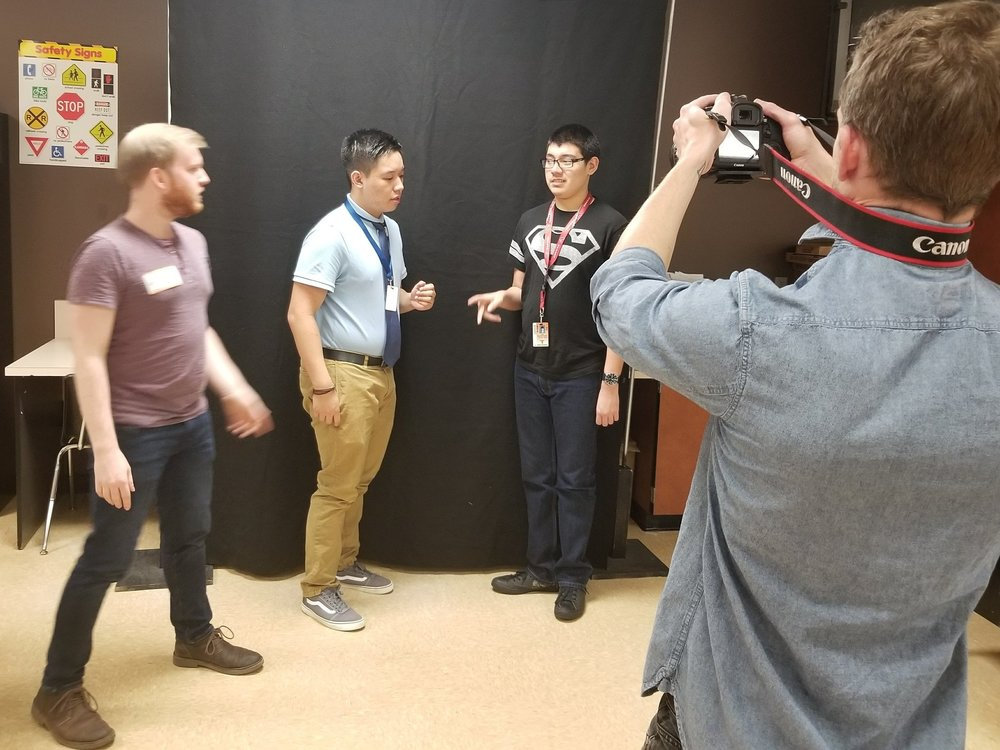 Two students act out a scene as the director and filmmaker work with them.