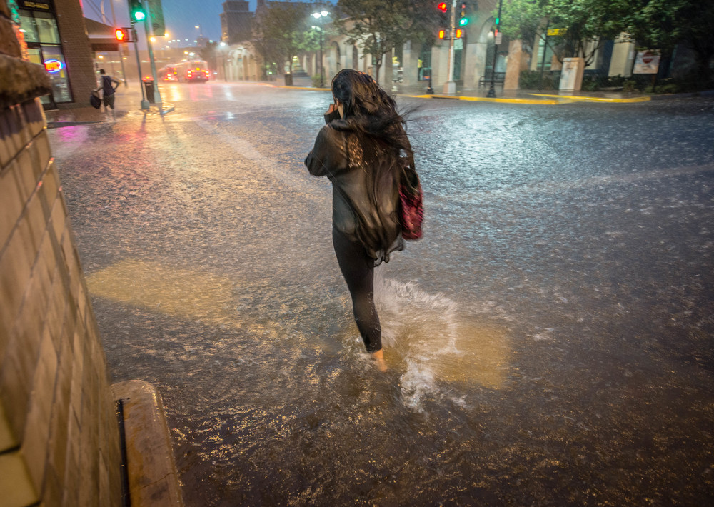 A woman walks across an intersection in downtown Albuquerque during a record storm.