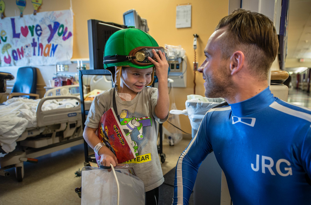 A kid at UNM's Children's hospital gets a visit from local jockeys who brought gifts and smiles.