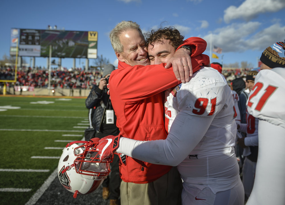 Coach Bob Davie hugs his player shortly before the final whistle  as the Lobos defeat University of Texas San Antonio.