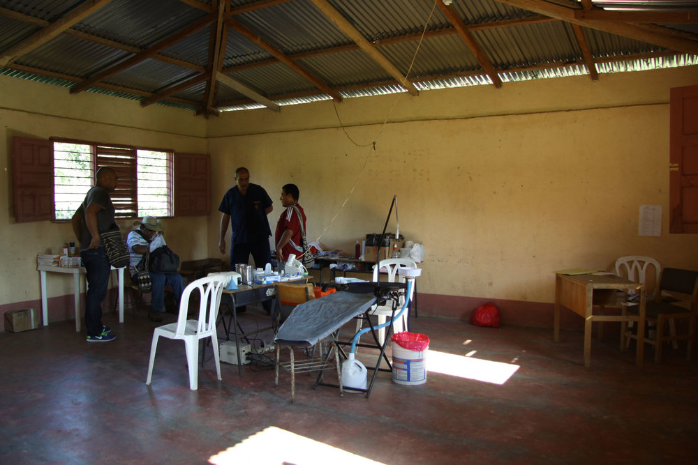 Travelling dental office set up in the school, Carlos the dentist in blue standing in the middle.