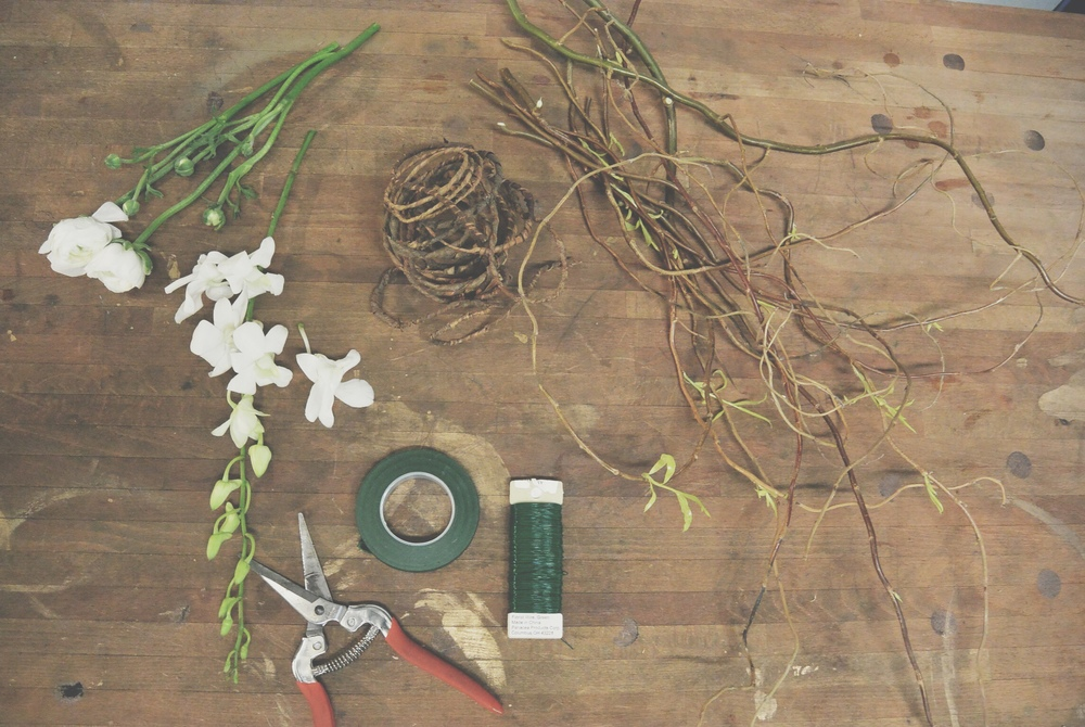 Okay, here's what you need: Some of your favorite flowers Curly willow branches (which you can find here) Covered wire (like this one here)  Floral tape Floral wire Garden shears