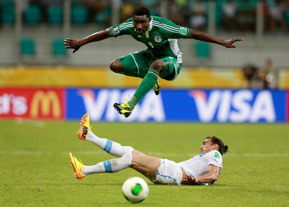 Joseph Akpala of Nigeria skips over a tackle from Martin Caceres of Uruguay during the FIFA Confederations Cup at Estadio Octavio Mangabeira, Salvador, Brazil