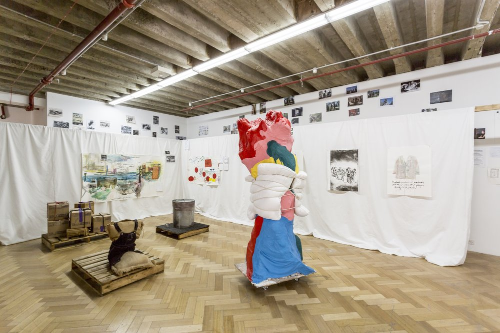 (Far Left) 21st C pedagogic process, found-materials stage design, 1950's Fruit Boxes,  2017, [re-installation instructions: requested seven boxes from Mac Donalds (take those given)], rope, gaffa tape, 'ethics guilt' tubing, glue, newspaper, found palette. Dimensions 1050 x 1100 x 1002 mm.  (Middle)  My life as a wharfie learnerar,  2017, hessian sack, and twine wadding and newspaper, purchased girl overall dress, found crate, 810 x 800 x 1010 mm.     (Back Middle) Swish or Swill, 2017. Found tin can, found tin cup, crate, carpet tiling, water and asbestos like talcum powder, 1200 X 900 X 1200 mm.   (Right) Education's blood with water viaduct and soft cell stitches , 2017, cardboard tubing, gauze from previous sculpture, backdrop material, plaster, house paint, clear Perspex single filing cabinet, curriculum documentation, rope, cardboard tubing, elastic, pillows, 2050 X 600 X 450mm. Image: Christo Crocker
