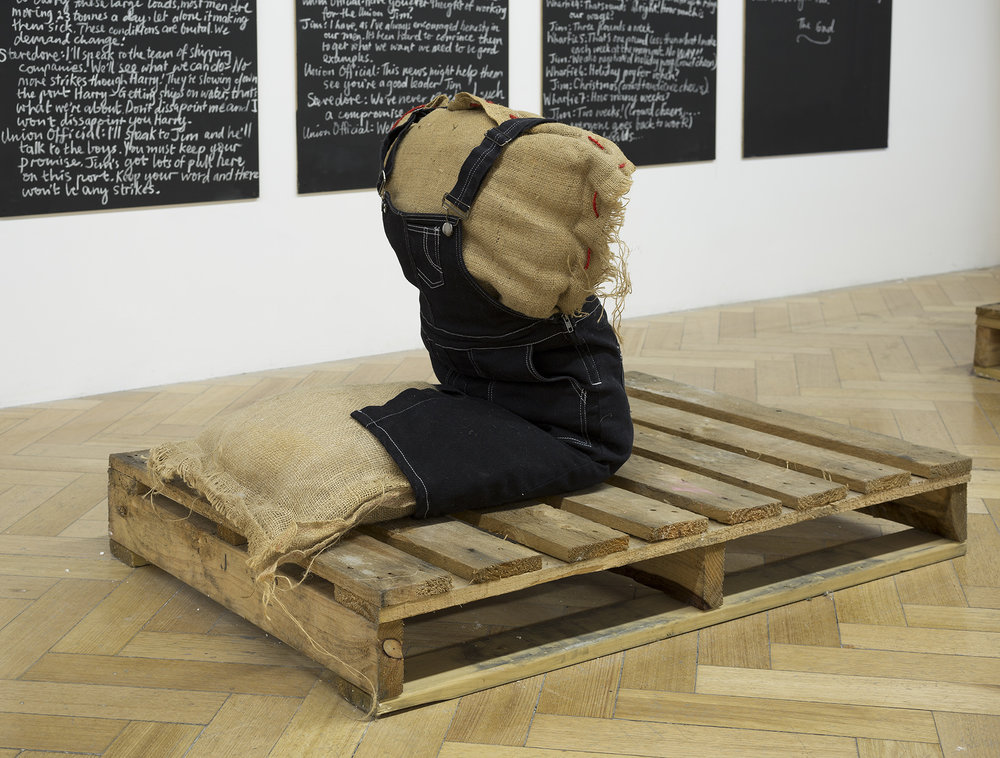 My life as a wharfie learnerar, 2017, hessian sack, and twine wadding and newspaper, purchased girl overall dress, found crate, 810 x 800 x 1010 mm. Westspace Gallery.Image: Christian Capurro.