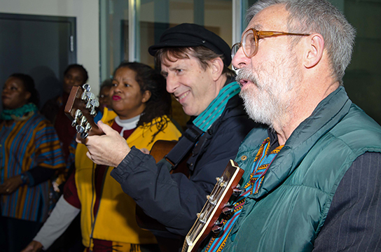 Musicians sing and strum guitar at a vigil held for Nelson Mandela at the South African Embassy.