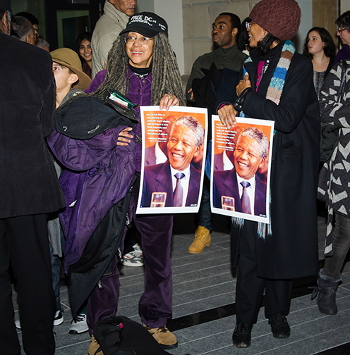 Attendees to the vigil for Nelson Mandela hold posters with his image.